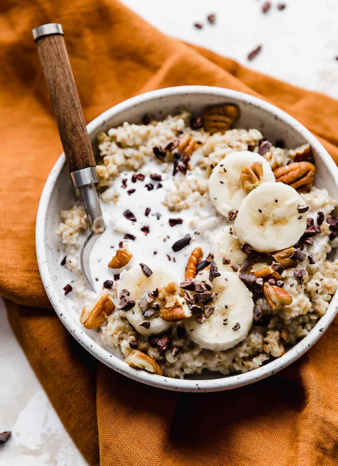 A bowl of steel cut oats on top of an amber colored napkin.