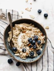 A bowl of Steel Cut Oats on a white background with blueberries and nuts.