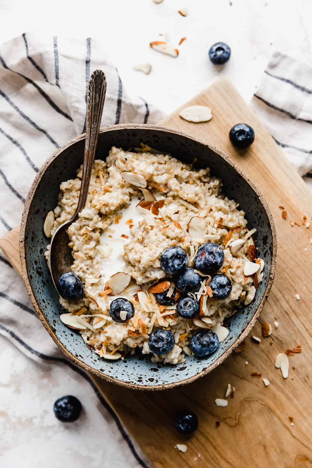A bowl of steel cut oats topped with blueberries, sliced almonds, and milk.