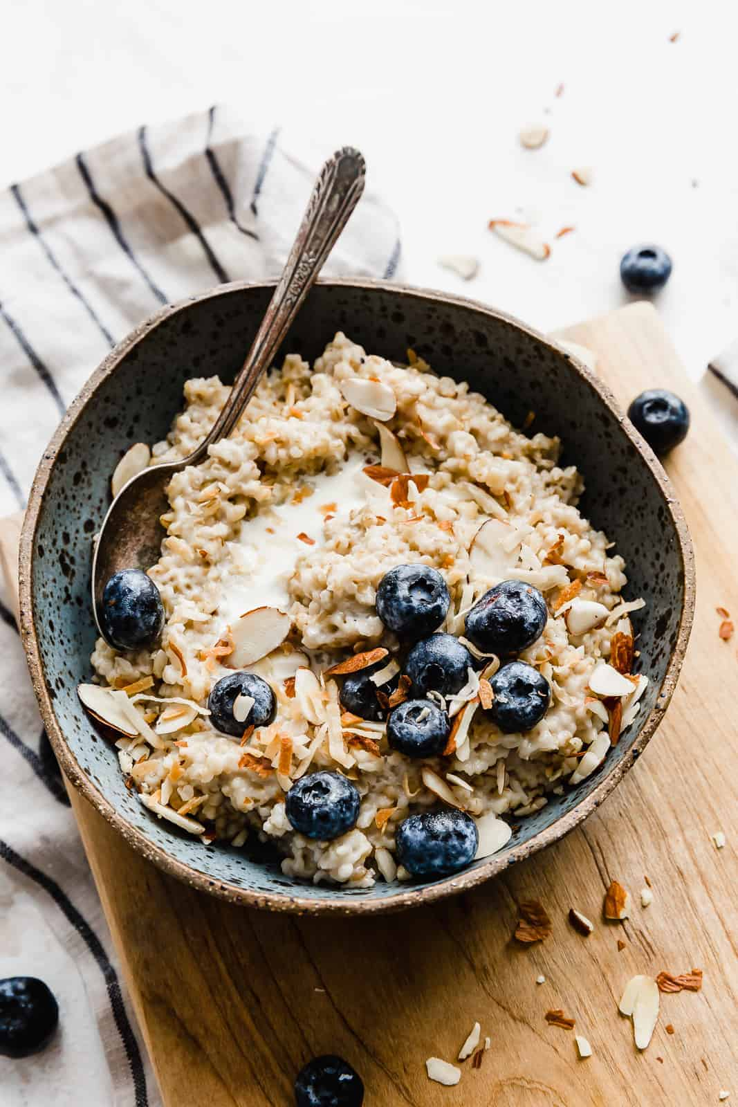 A bowl of steel cut oats topped with blueberries, almonds, and milk.