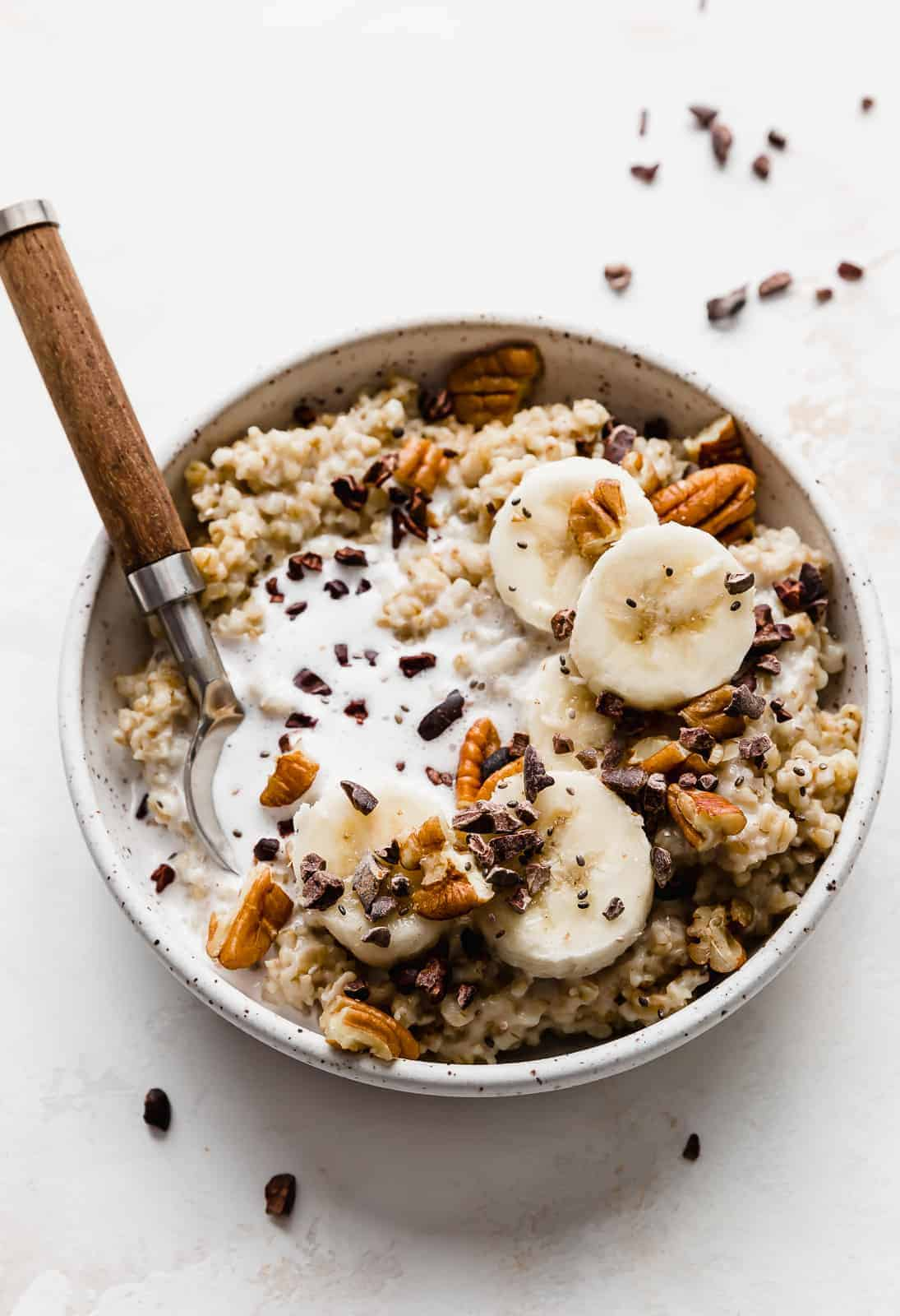 A bowl of steel cut oats topped with sliced bananas, pecans, and cocoa nibs.