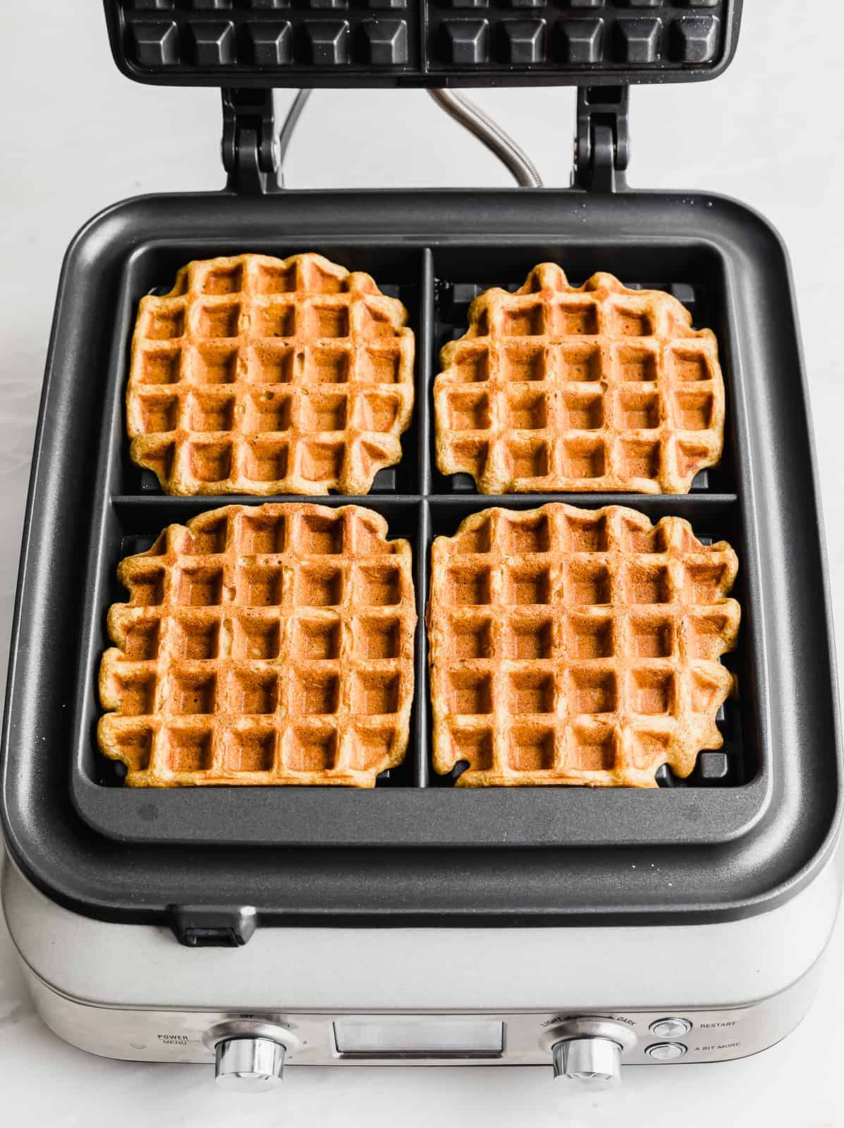 4 square pumpkin waffles in a square waffle iron.