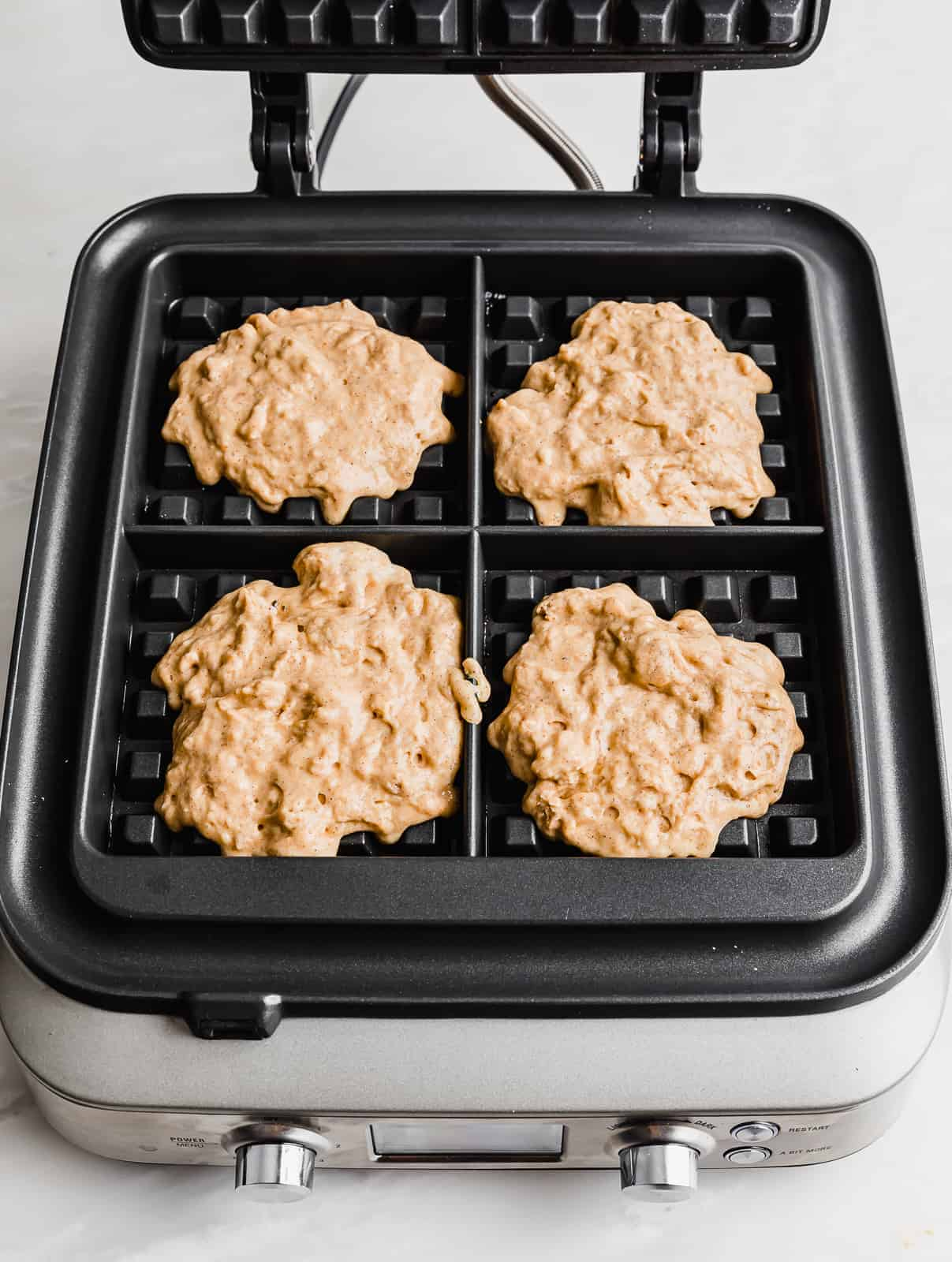 A square waffle iron with pumpkin waffle batter in the 4 waffle compartments.