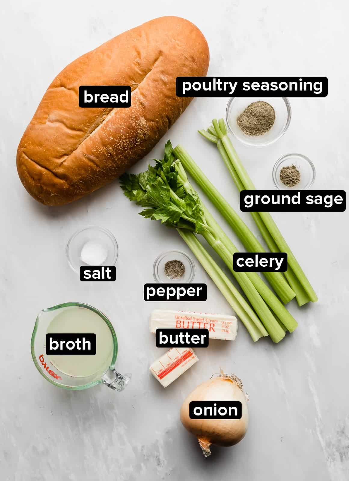 Ingredients used to make homemade thanksgiving stuffing on a marble counter.