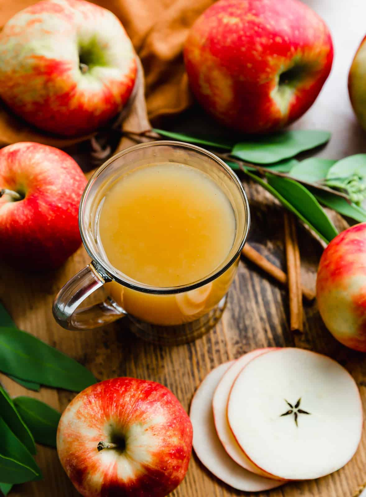 A cup of wassail surrounded by red apples.