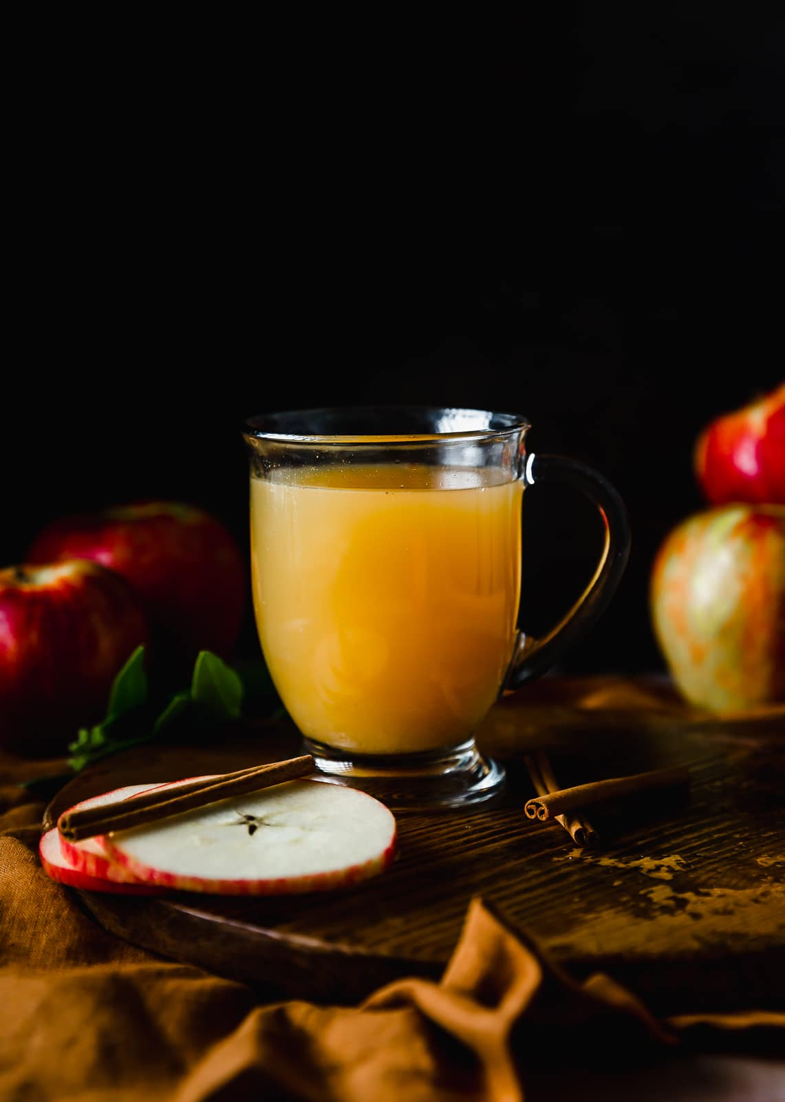 A glass of wassail against a black background with red apples around the edges of the photo.