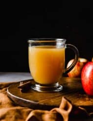 A glass of homemade wassail against a black background.