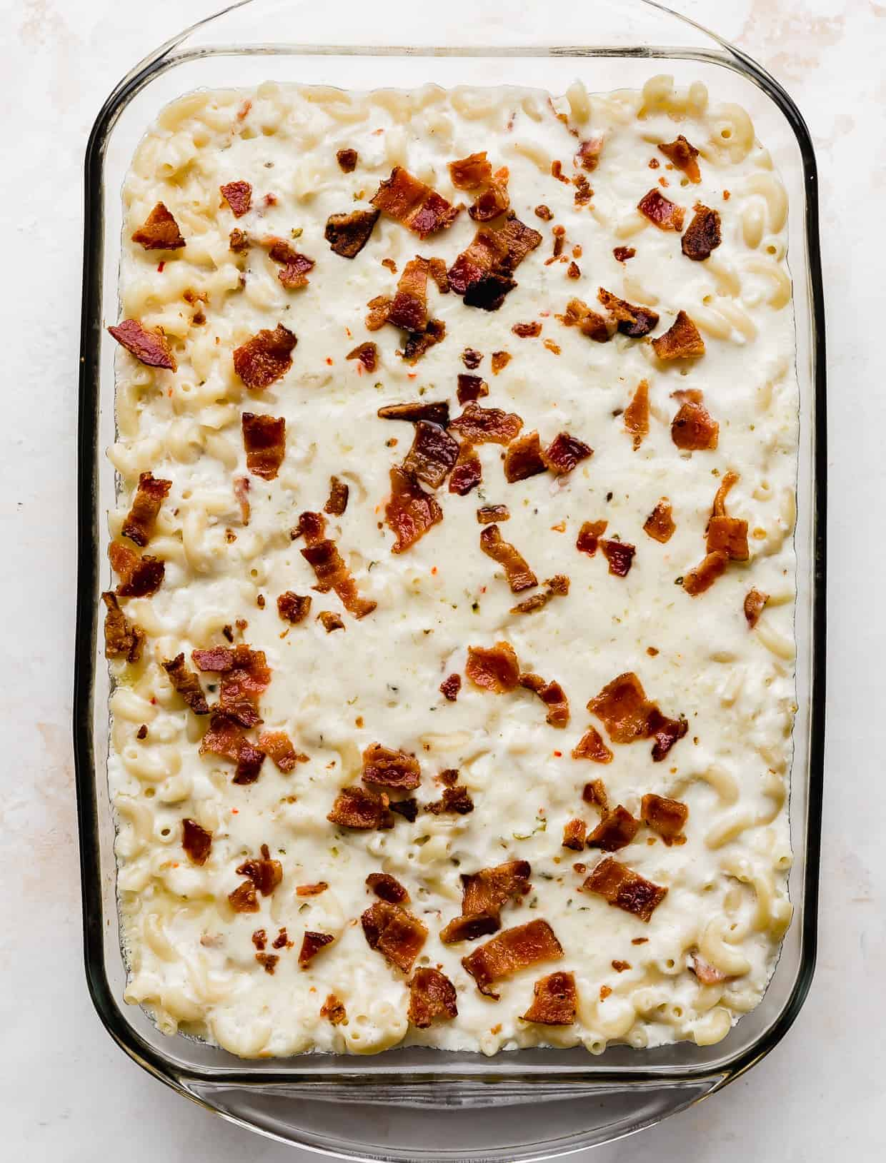Freshly baked Bacon Pepper Jack Mac and Cheese in a casserole dish against a white background.
