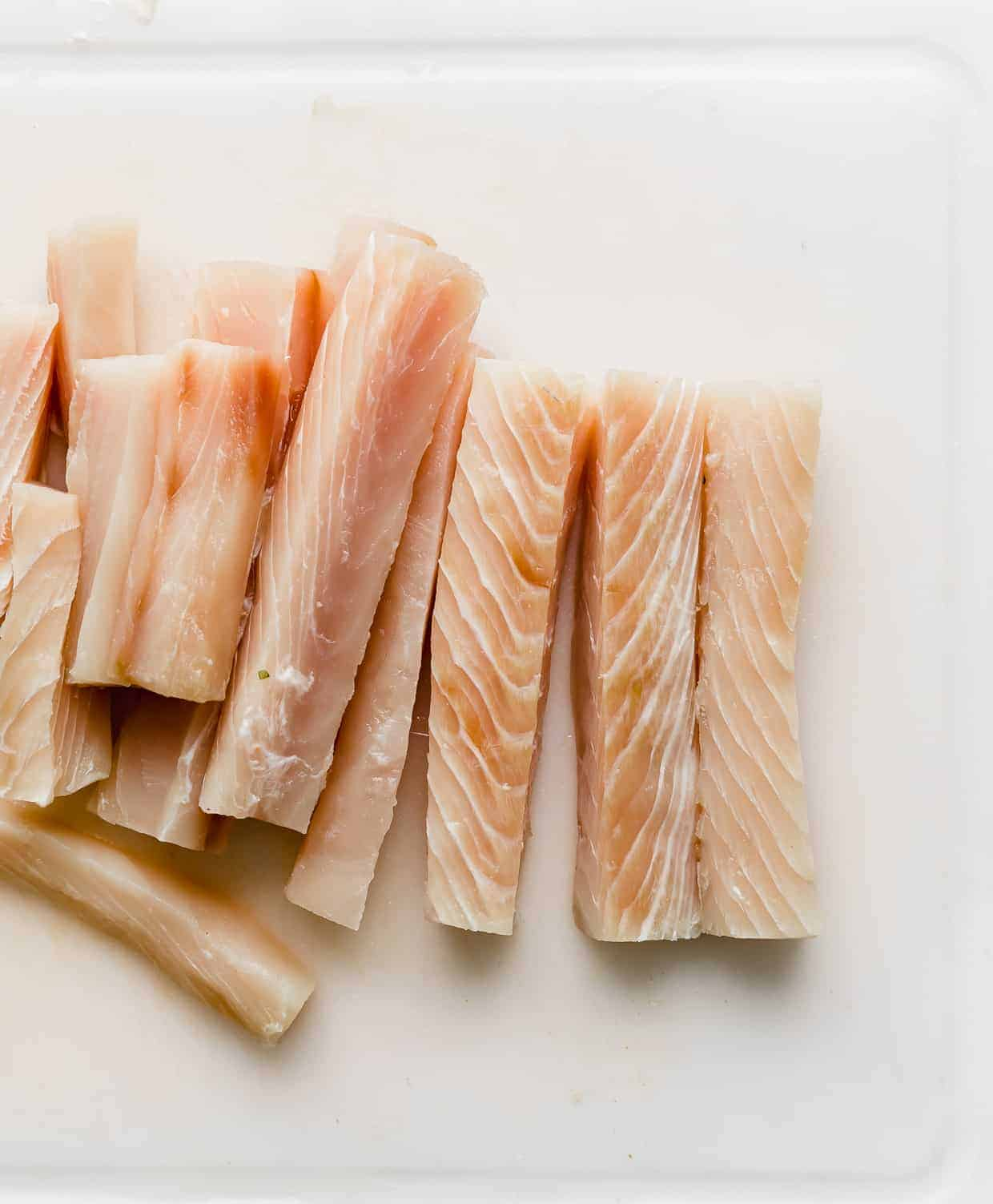 Mahi Mahi fish sliced into thin strips which are resting on a white cutting board.
