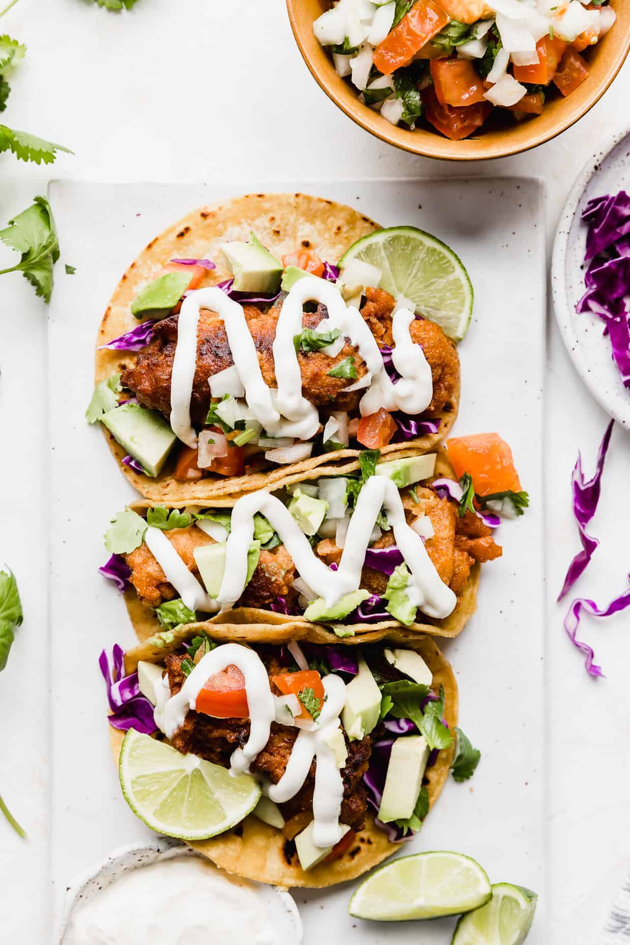 Three Baja Fish Tacos on a white plate topped with lime, avocado, white sauce, and cabbage.