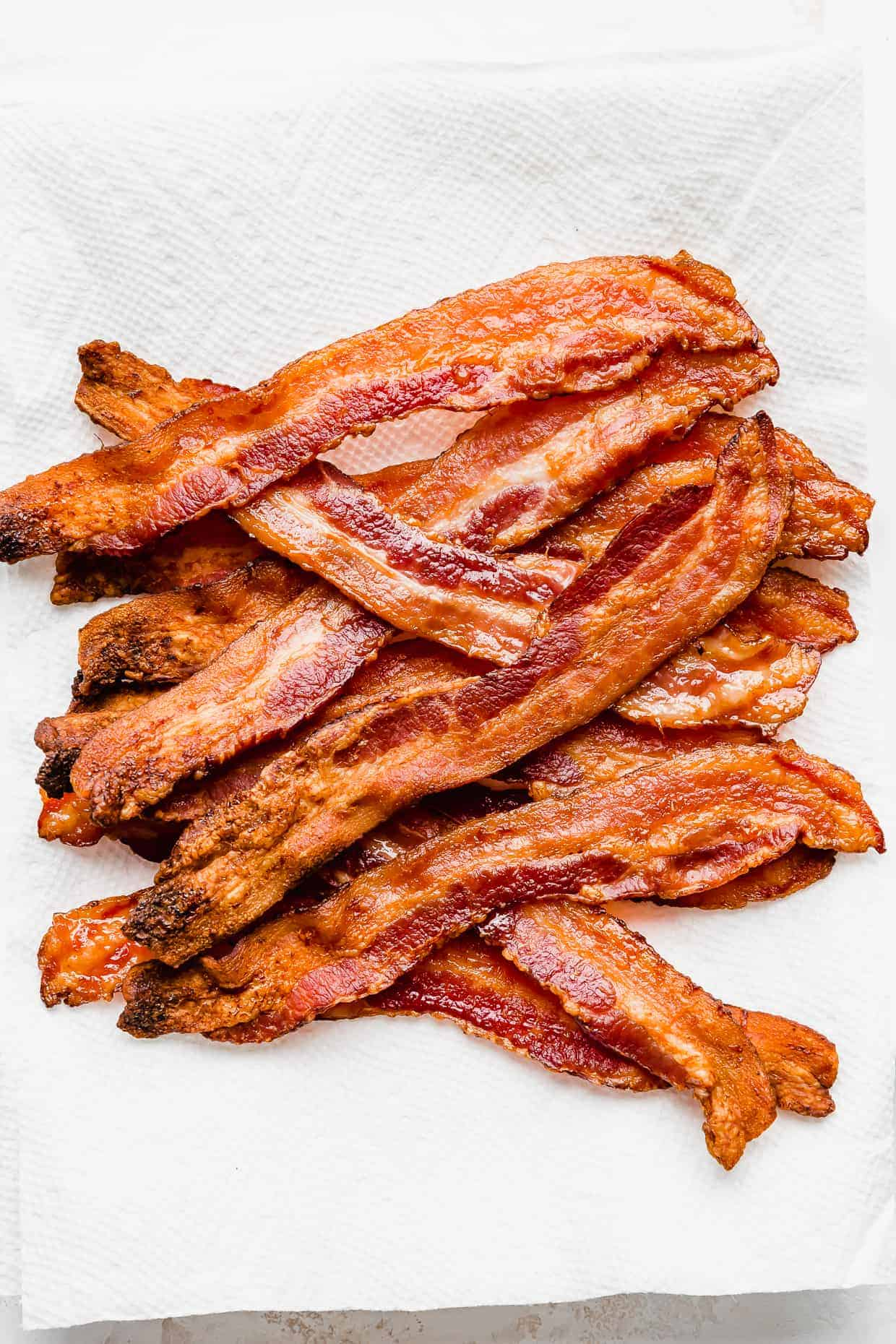 Strips of crispy bacon on a white paper towel.