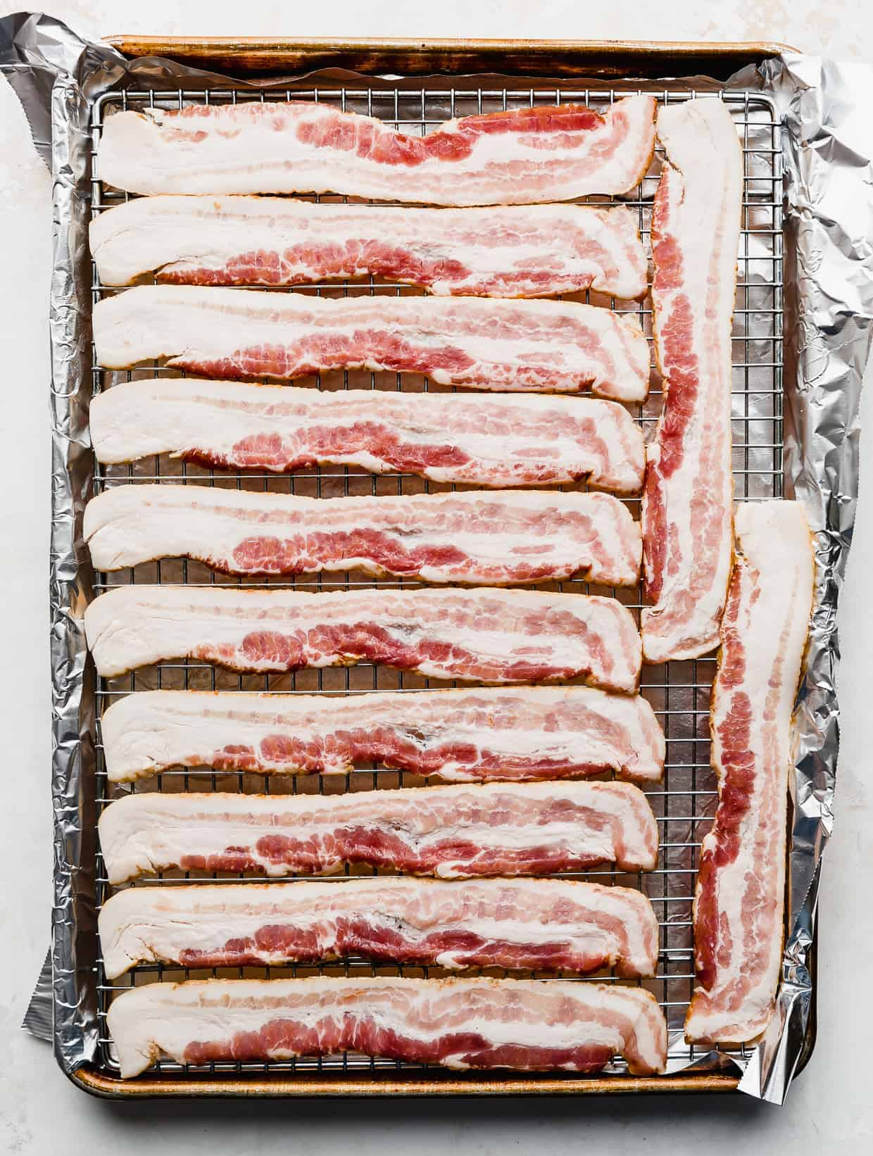 Raw bacon lined on a wire rack resting in a baking sheet.