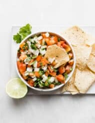 A bowl of fresh pico de Gallo with tortilla chips on the right side of the bowl.