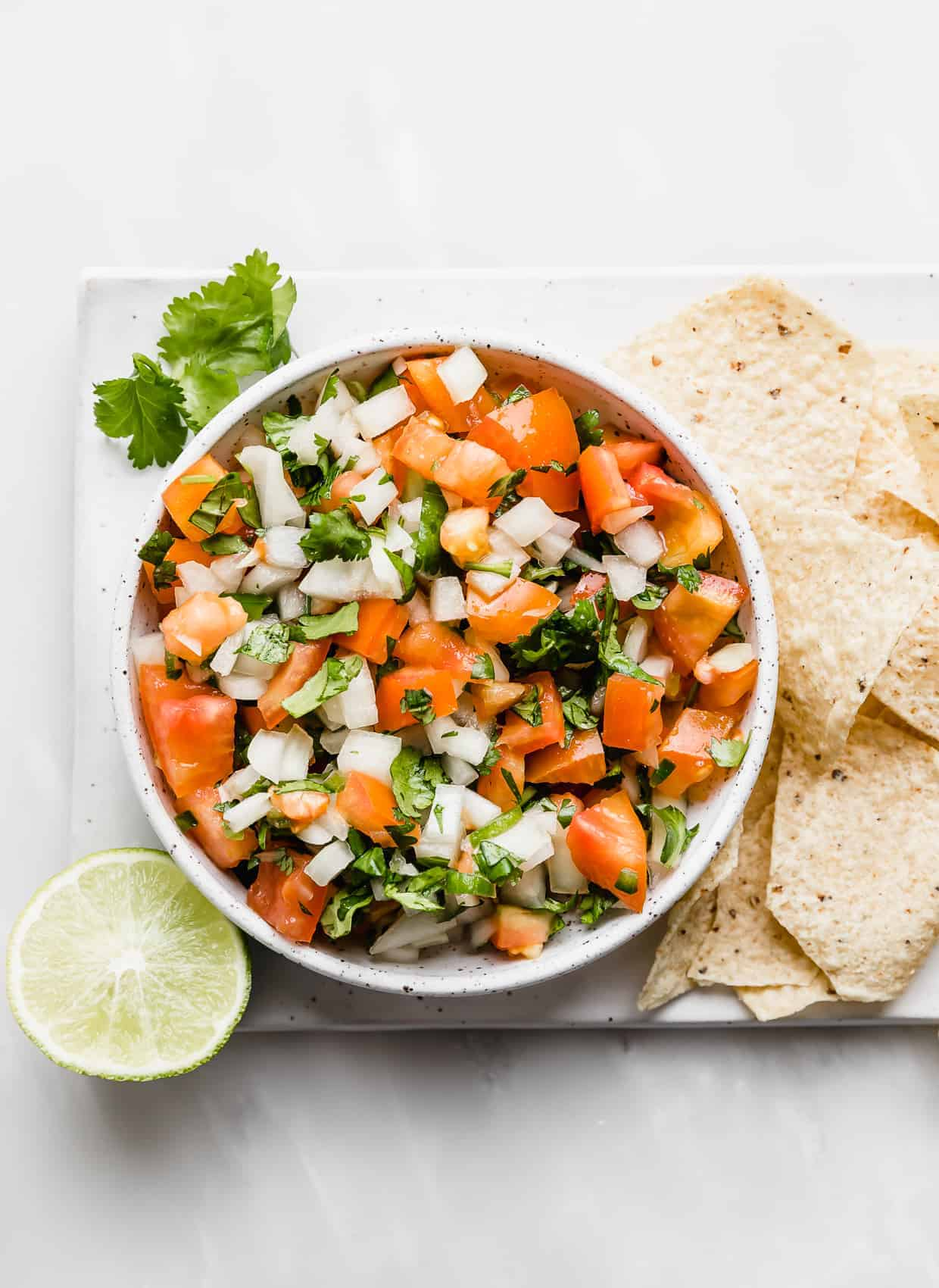 A bowl of Pico de Gallo surrounded by tortilla chips.