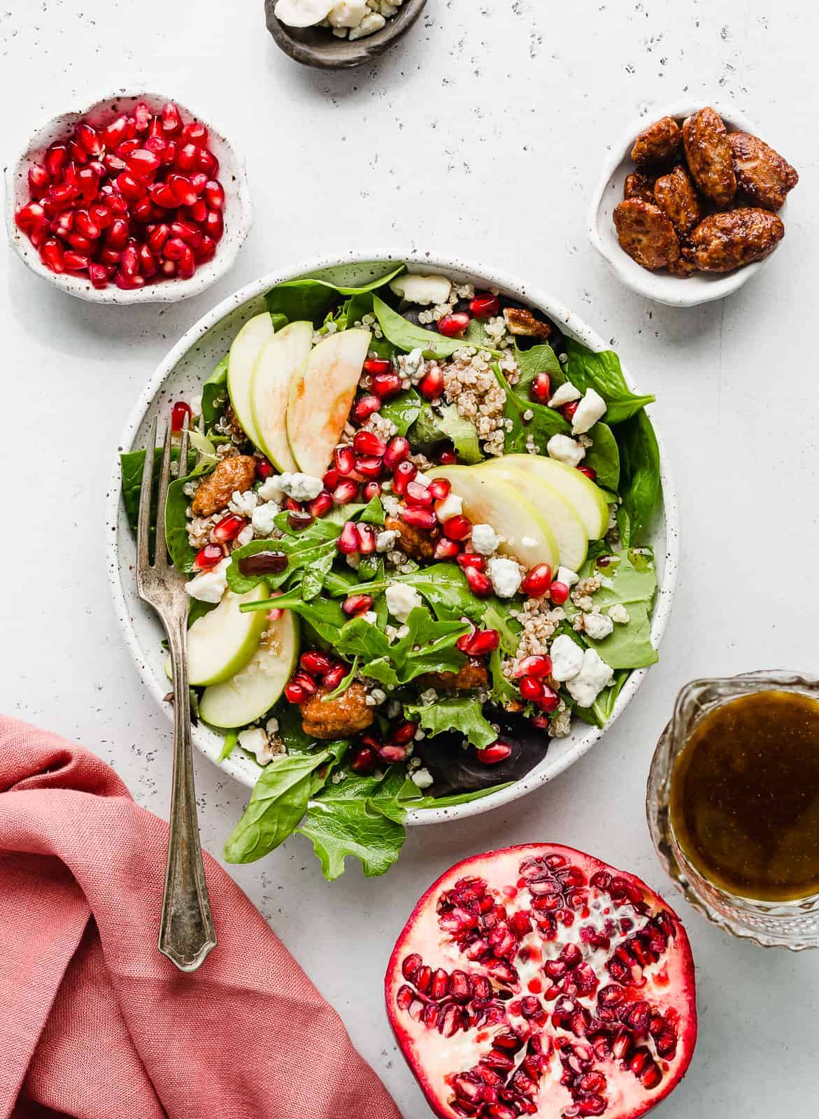 A plate of Pomegranate Salad topped with nuts, cheese, pomegranate arils, and chopped apples.