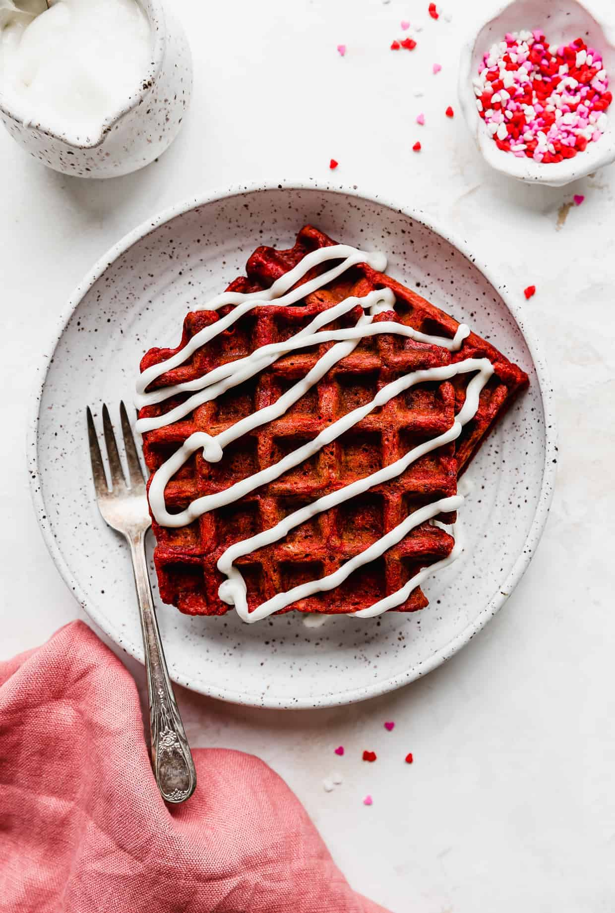 A white plate with 2 red velvet waffles on it drizzled in a white cream cheese glaze, against a white background.