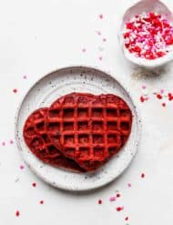 A heart shaped red velvet waffle on a white plate against a white background.