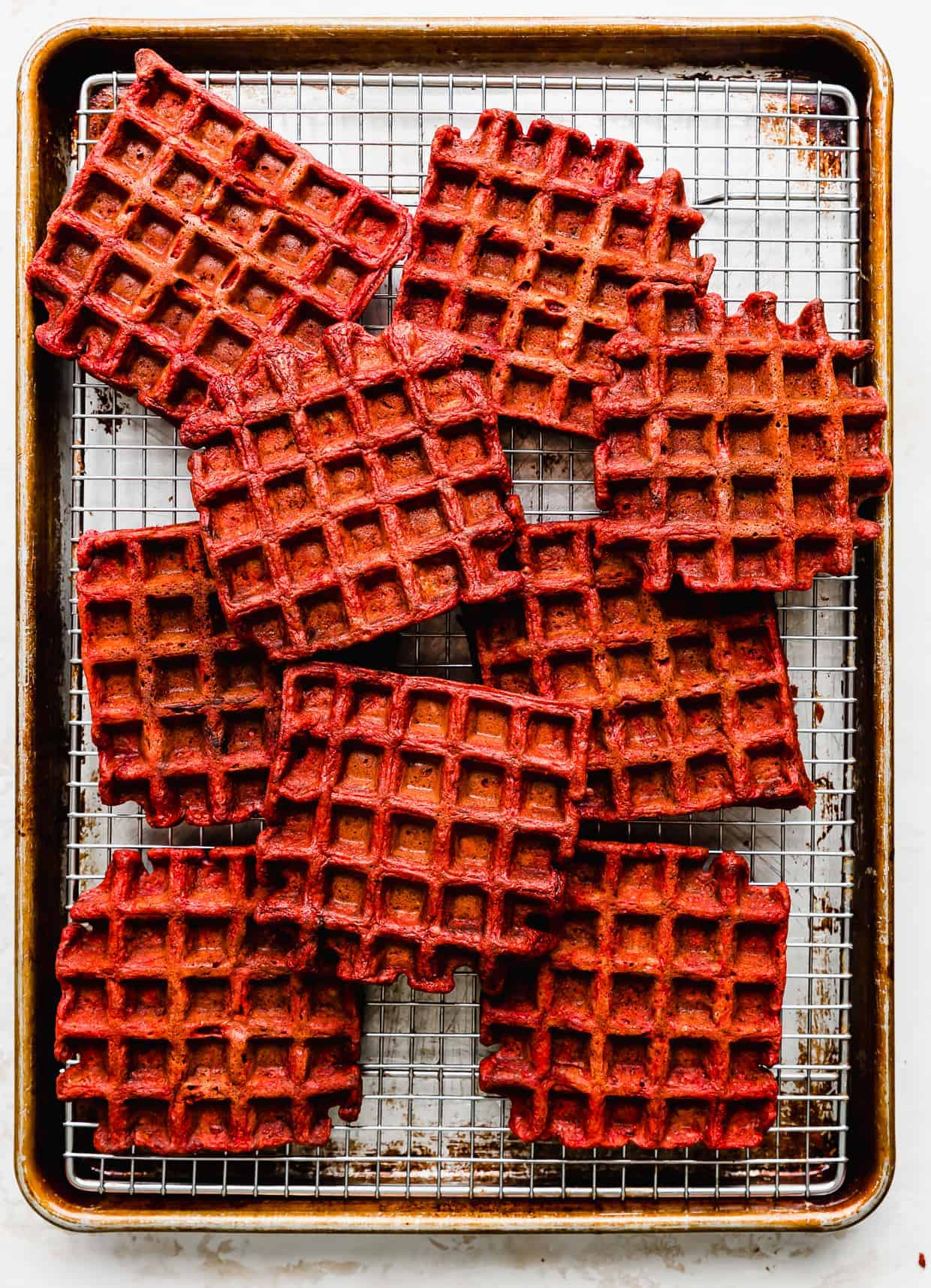 A baking sheet topped with a wire rack and square red velvet waffles on the rack.