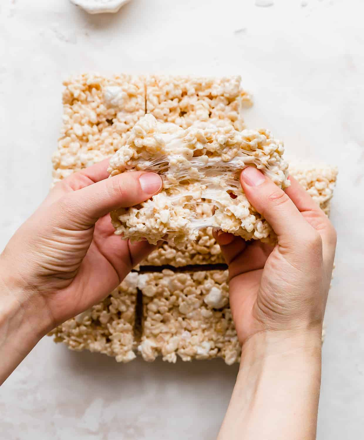 A pair of hands pulling a gooey Rice Krispie treat apart.
