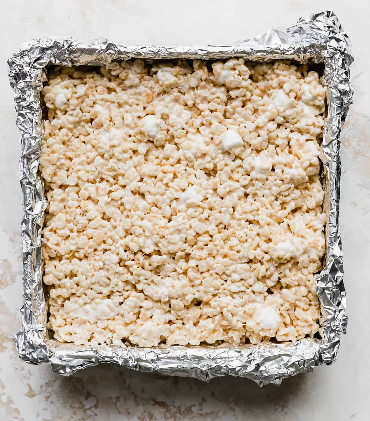 Salted Brown Butter Rice Krispie Treats pressed into a foil lined square pan against a white background.