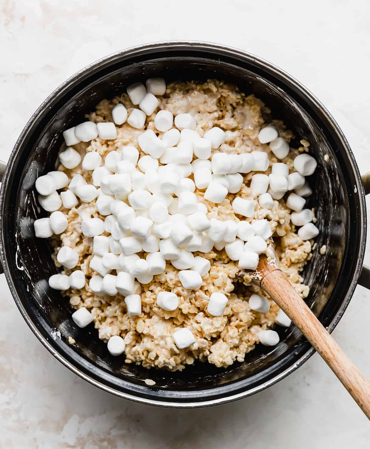 Mini marshmallows in a large pot, begin stirred into Rice Krispie treats.