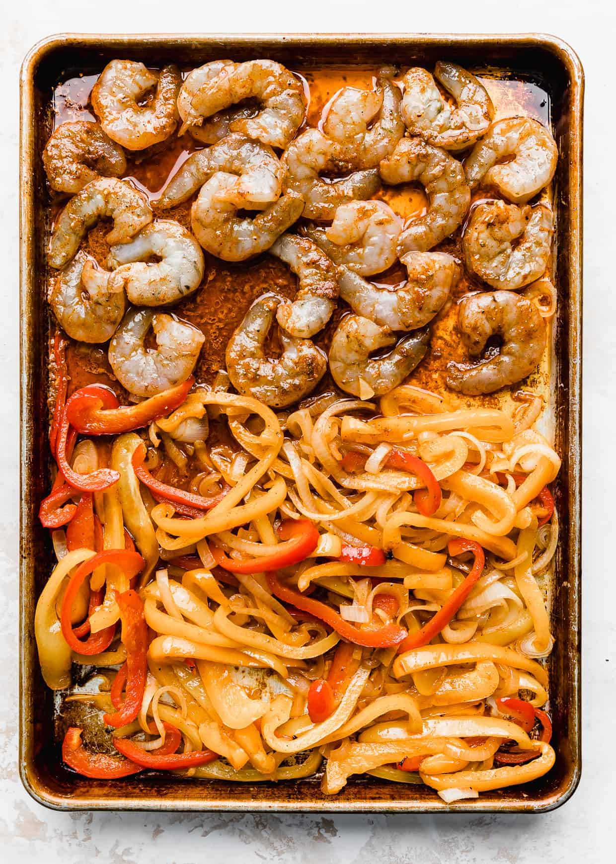 Shrimp and sliced peppers on a baking sheet against a white background.