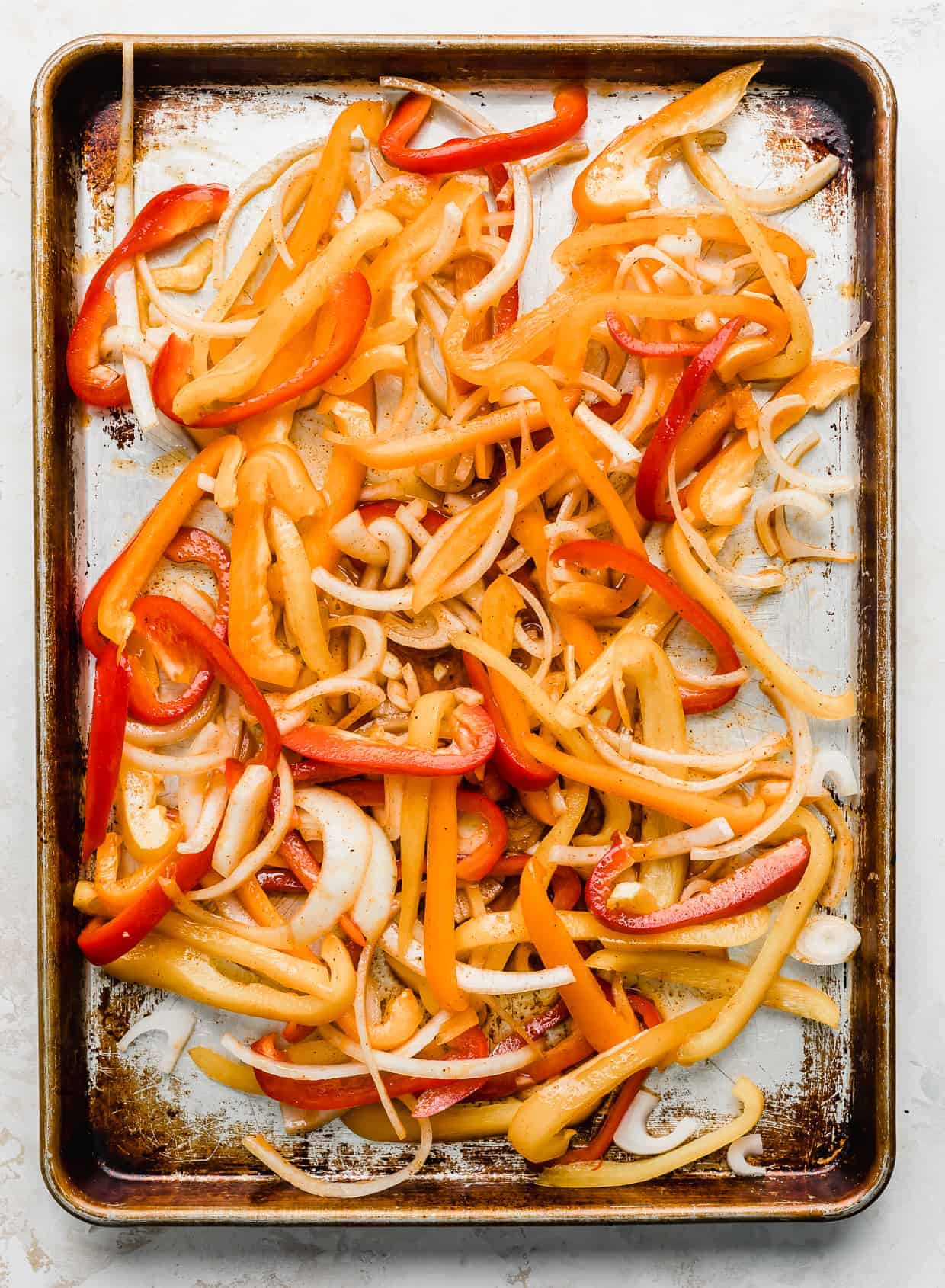 A baking sheet with sliced orange, red, and yellow peppers.