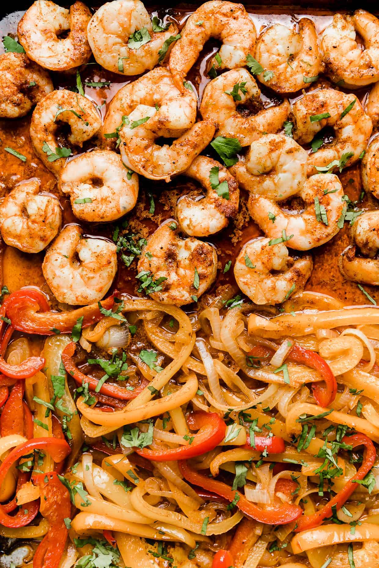 A close up photo of cooked shrimp and cooked sliced red, yellow, and orange peppers.