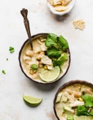 A bowl of Best White Chicken Chili against a white background, topped with cilantro, lime, and tortilla chips.