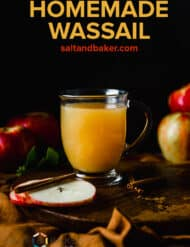 A clear mug full of amber colored Wassail drink against a black background.