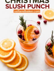 A glass full of an orange colored drink topped with rosemary and fresh cranberries.