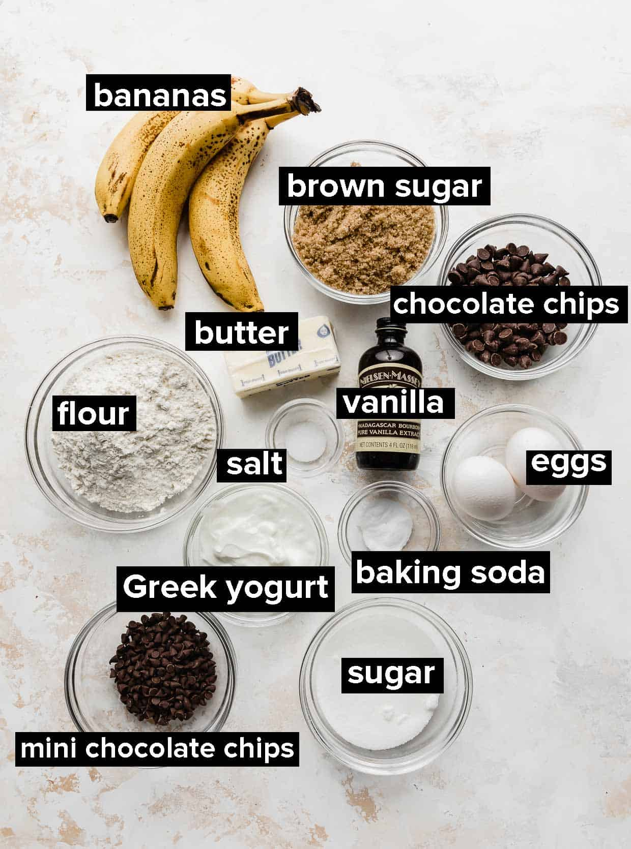 Ingredients used to make chocolate chip banana bread spread out on a white table.