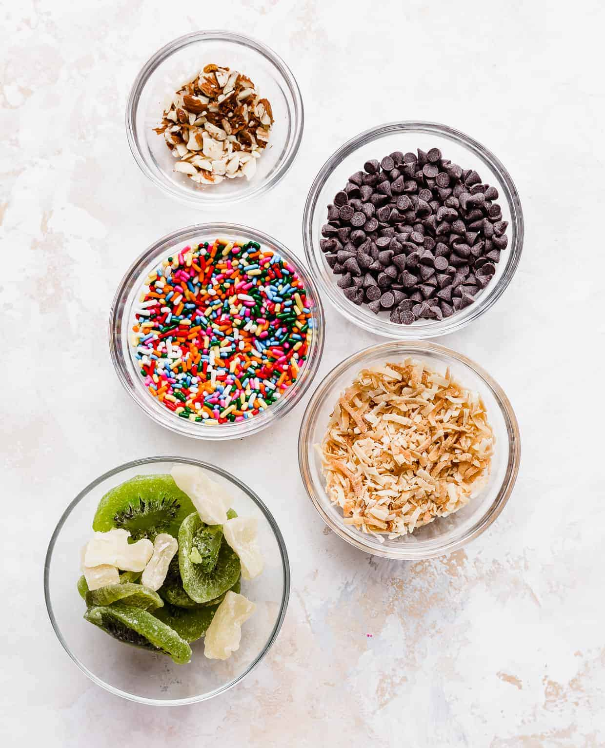 Glass bowls full of toppings such as sprinkles, toasted coconut, mini chocolate chips, dried fruit, and nuts.