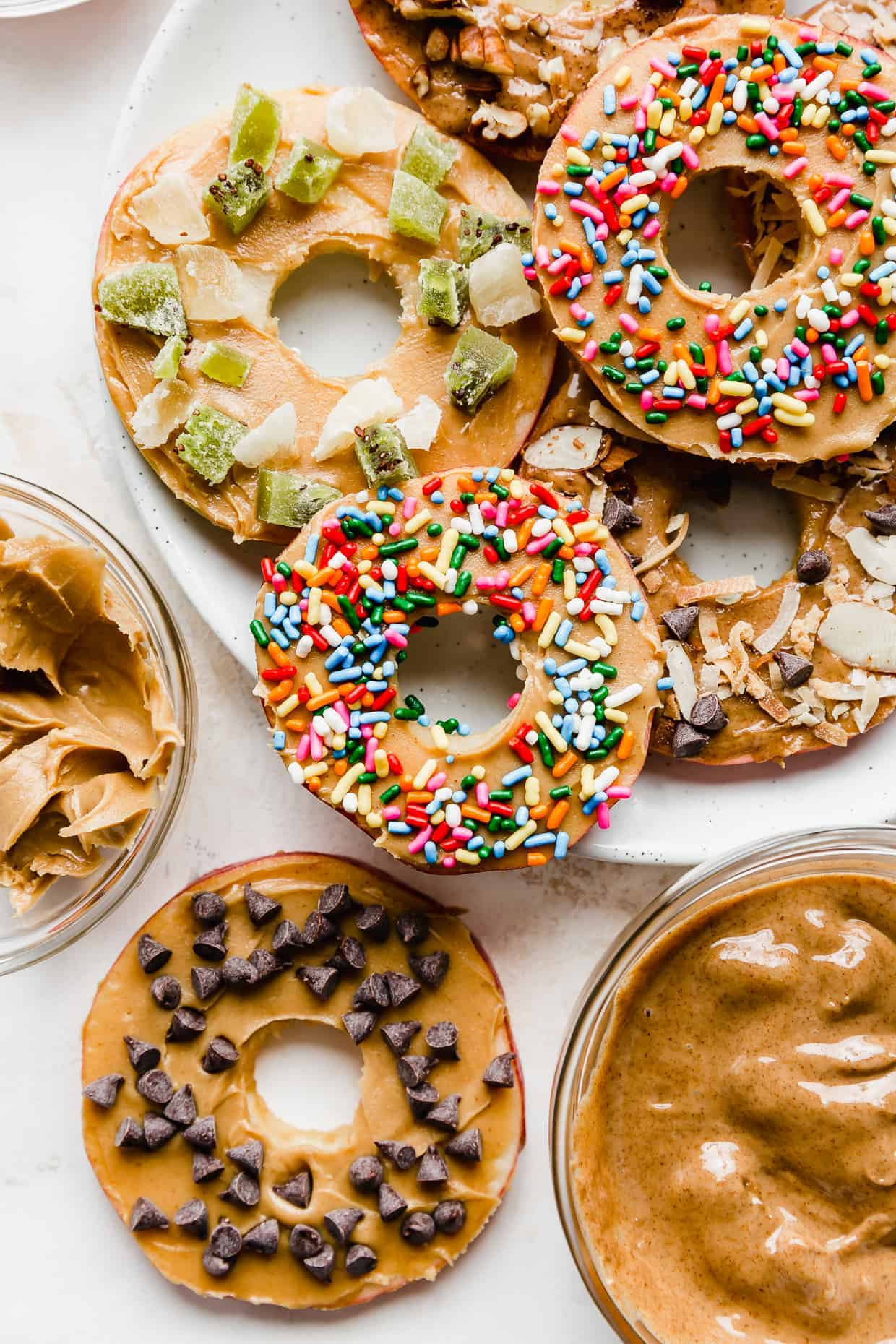 """Slices of apples cut into round """"donuts"""" topped with peanut butter, sprinkles, chocolate chips."""