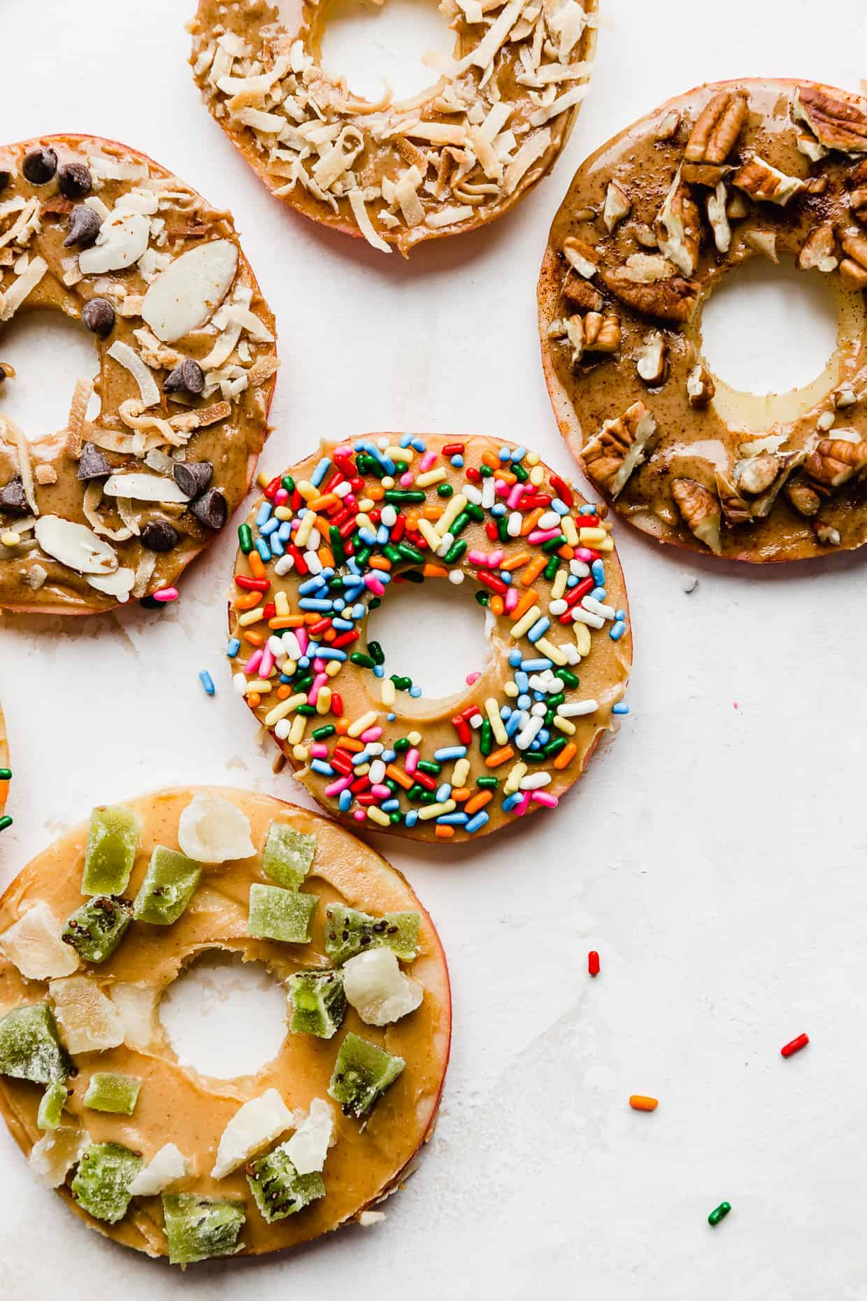 Donut Apples against a white background, with an array of toppings: sprinkles, nuts, chocolate.