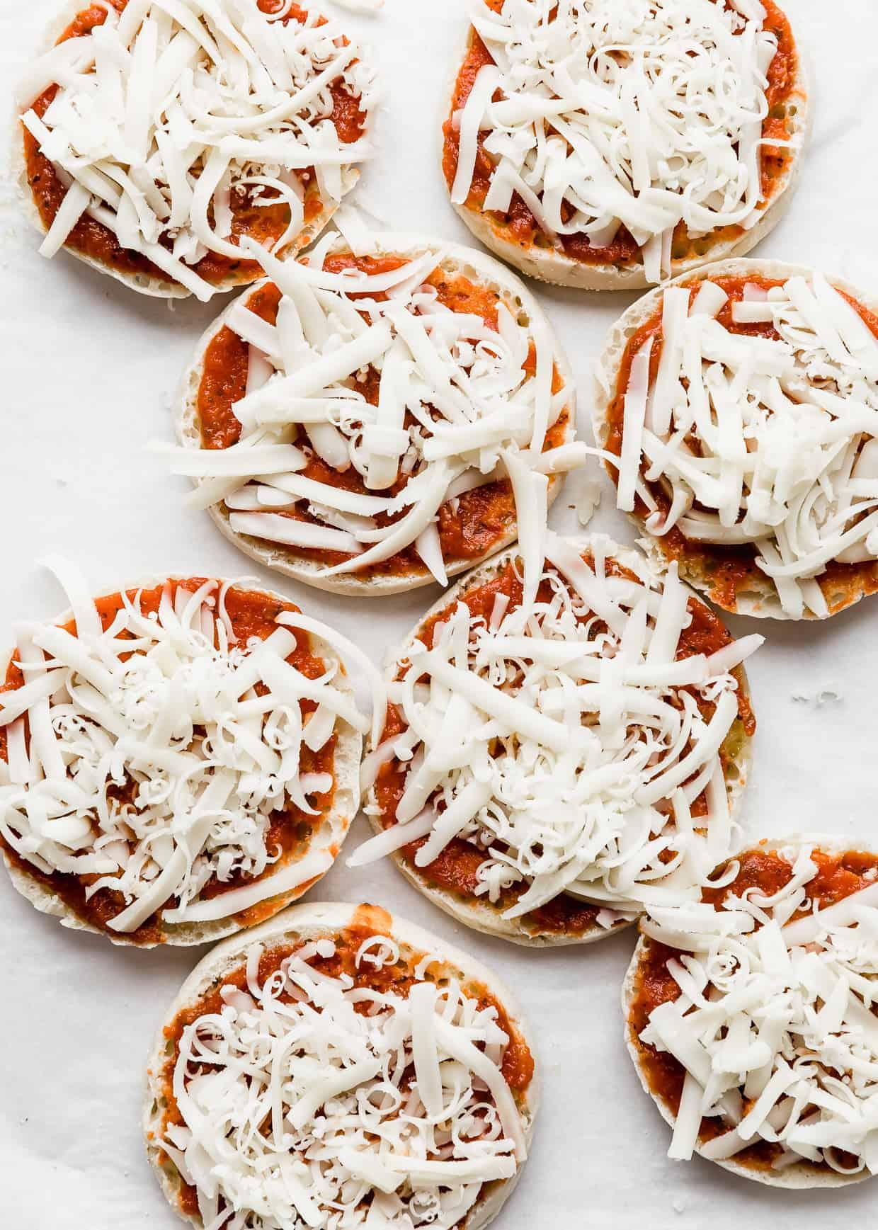 Shredded mozzarella overtop of eight English muffin halves.