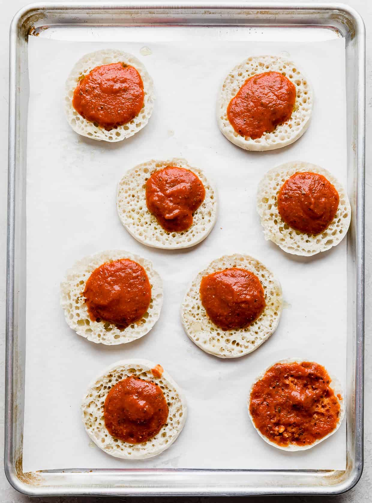 Pizza sauce dolloped on eight English muffin pizza halves.