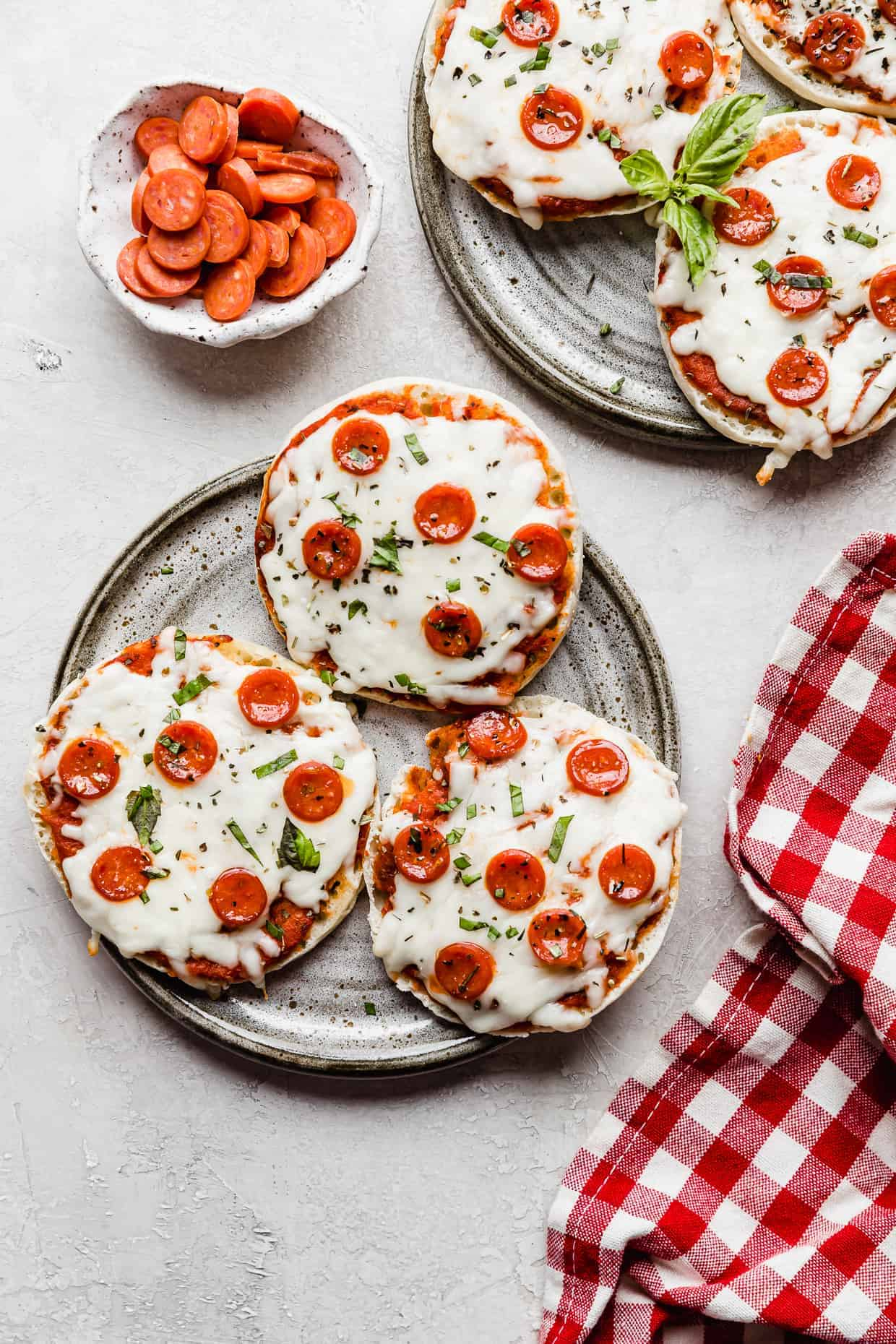 A gray plate with English muffin pizzas on it against a gray background.