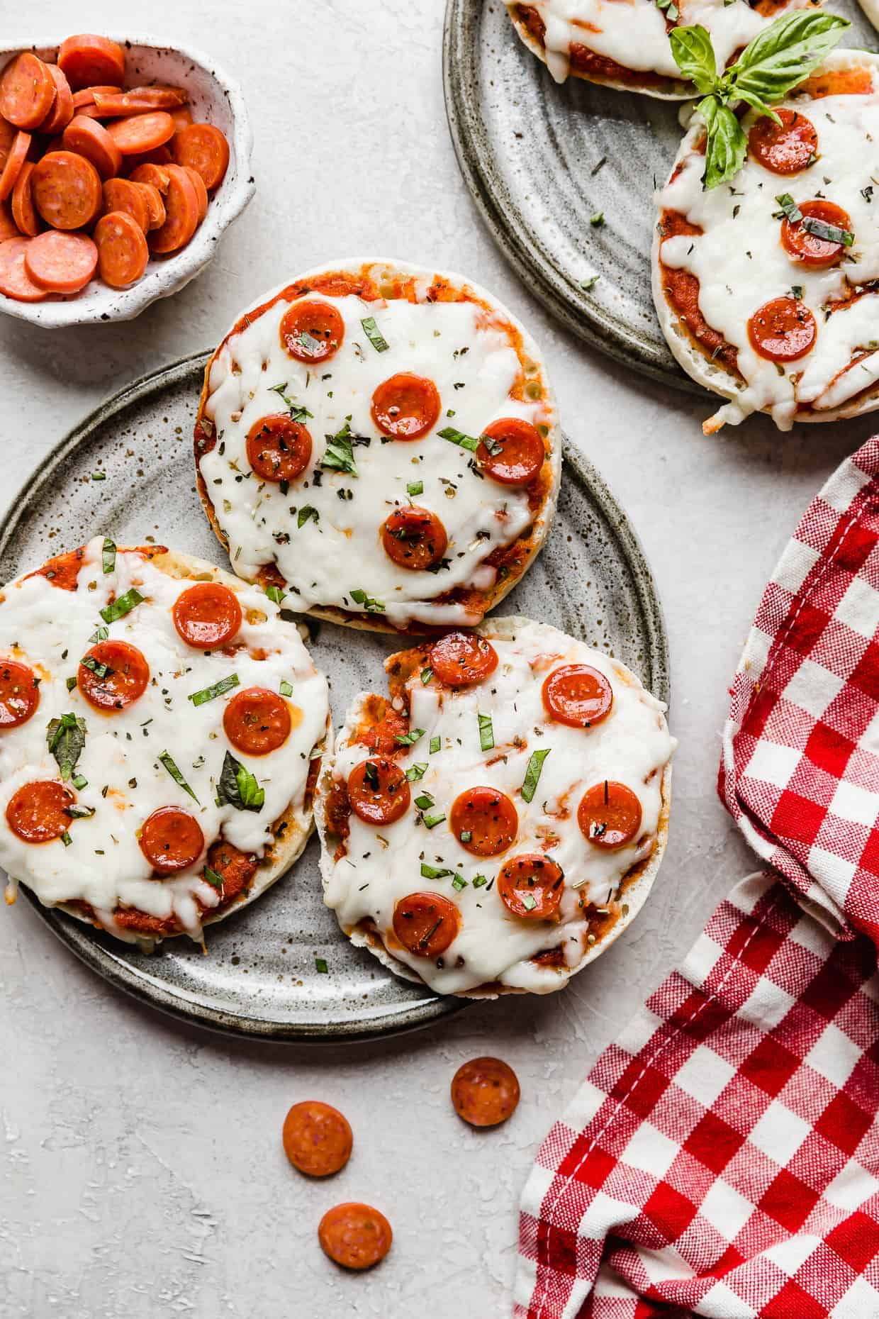 Three English muffin pizzas topped with mini pepperoni's on a gray plate.