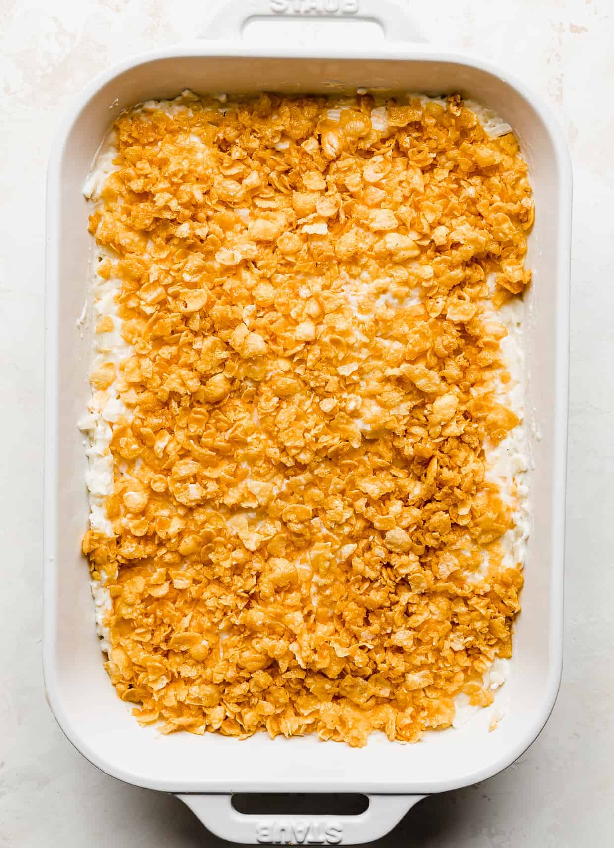 A casserole dish full of unbaked funeral potatoes topped with crushed cornflakes, against a white background.
