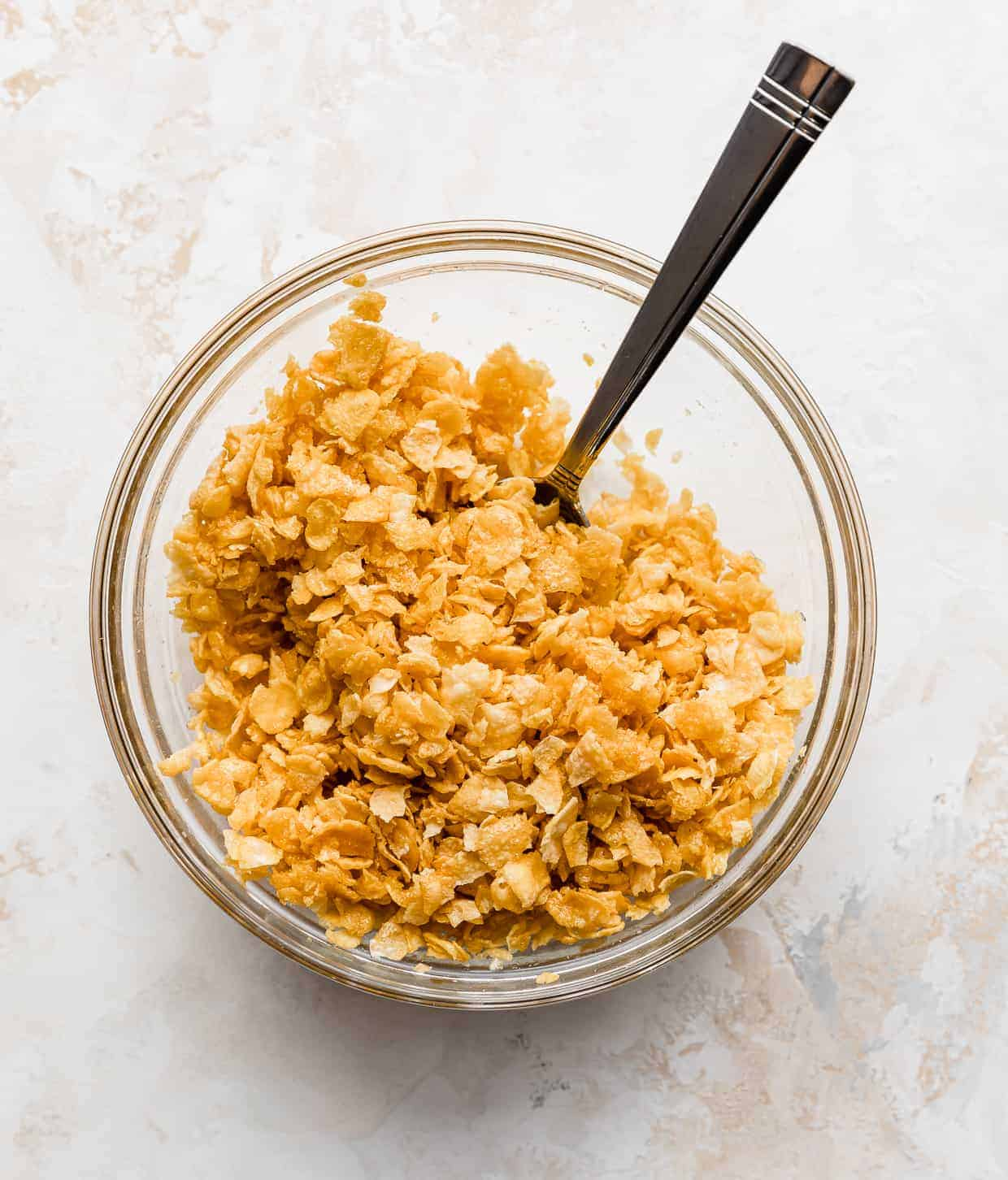 A glass bowl with crushed cornflakes in it.