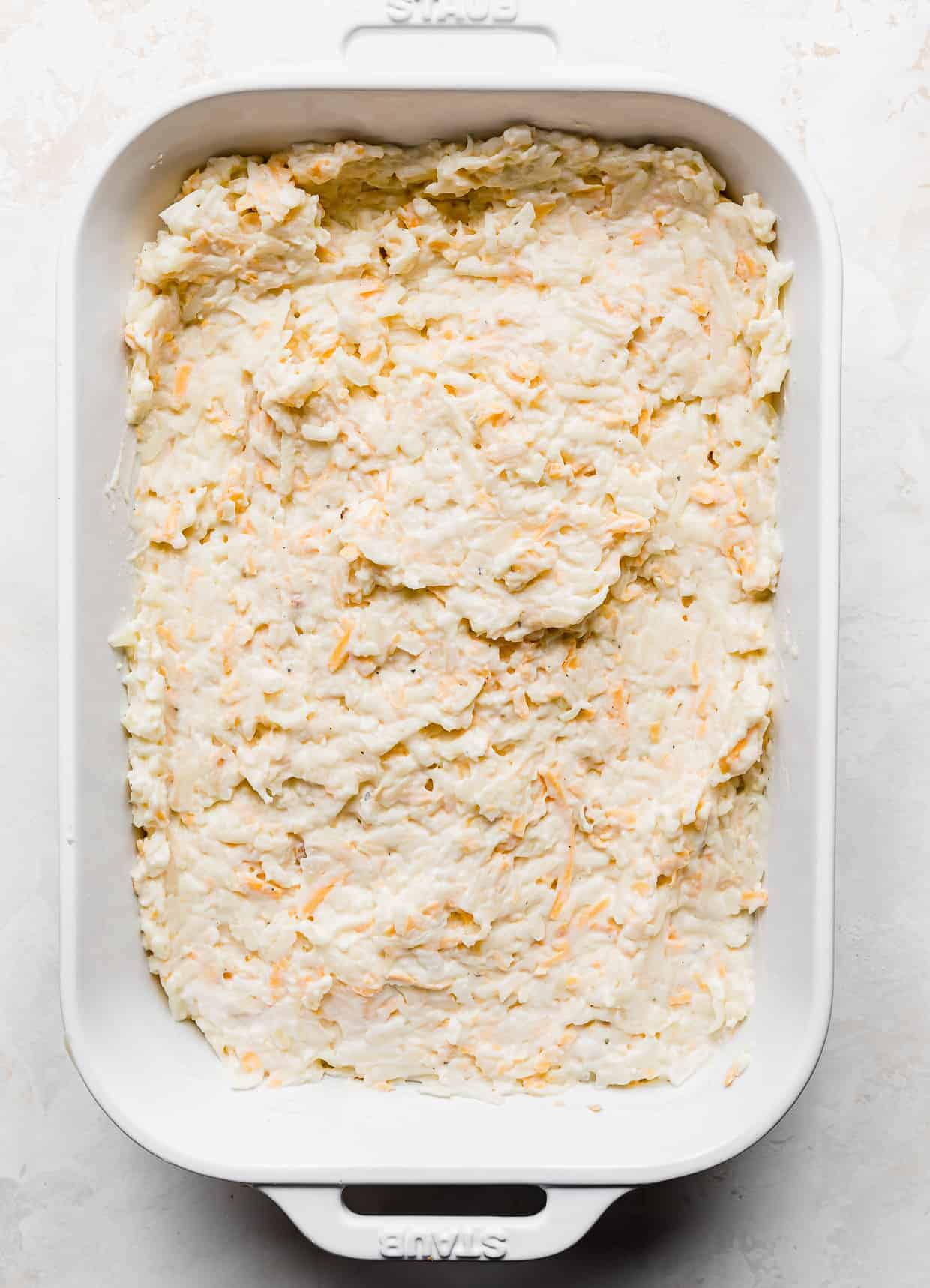 A white casserole dish full of leveled funeral potatoes against a white background.