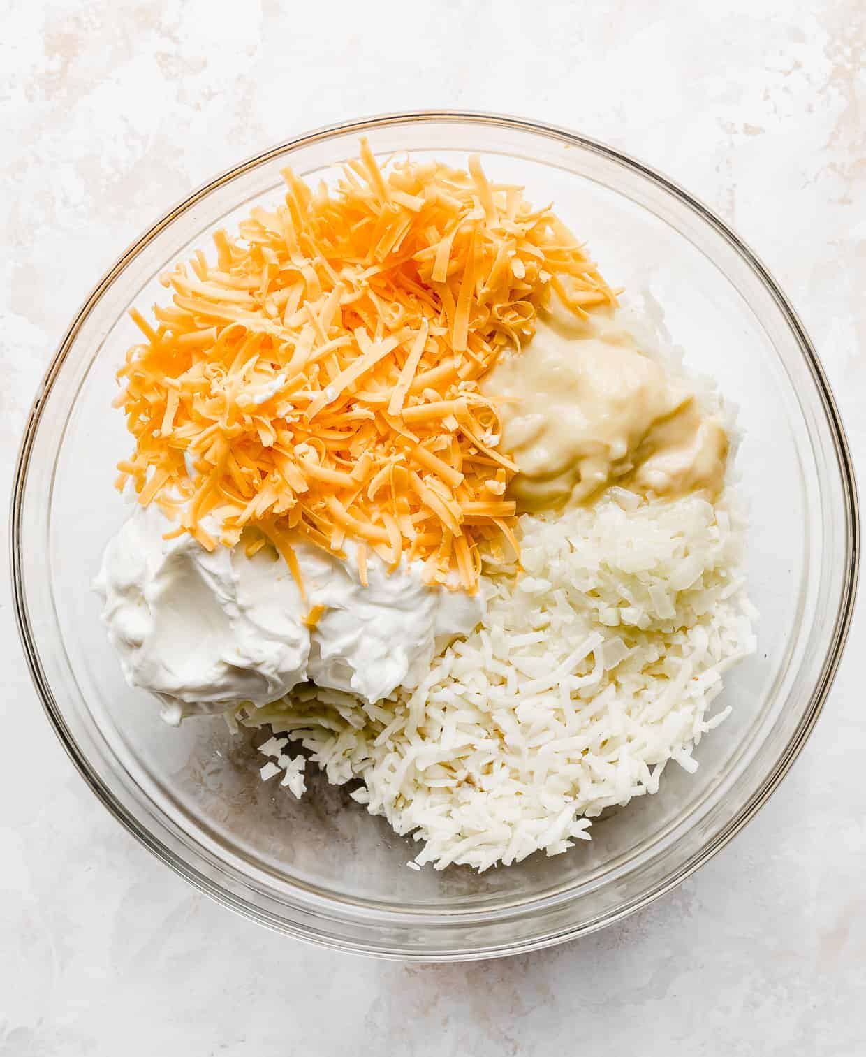 A large bowl full of shredded hashbrowns, cheddar cheese, sour cream, and cream of chicken.