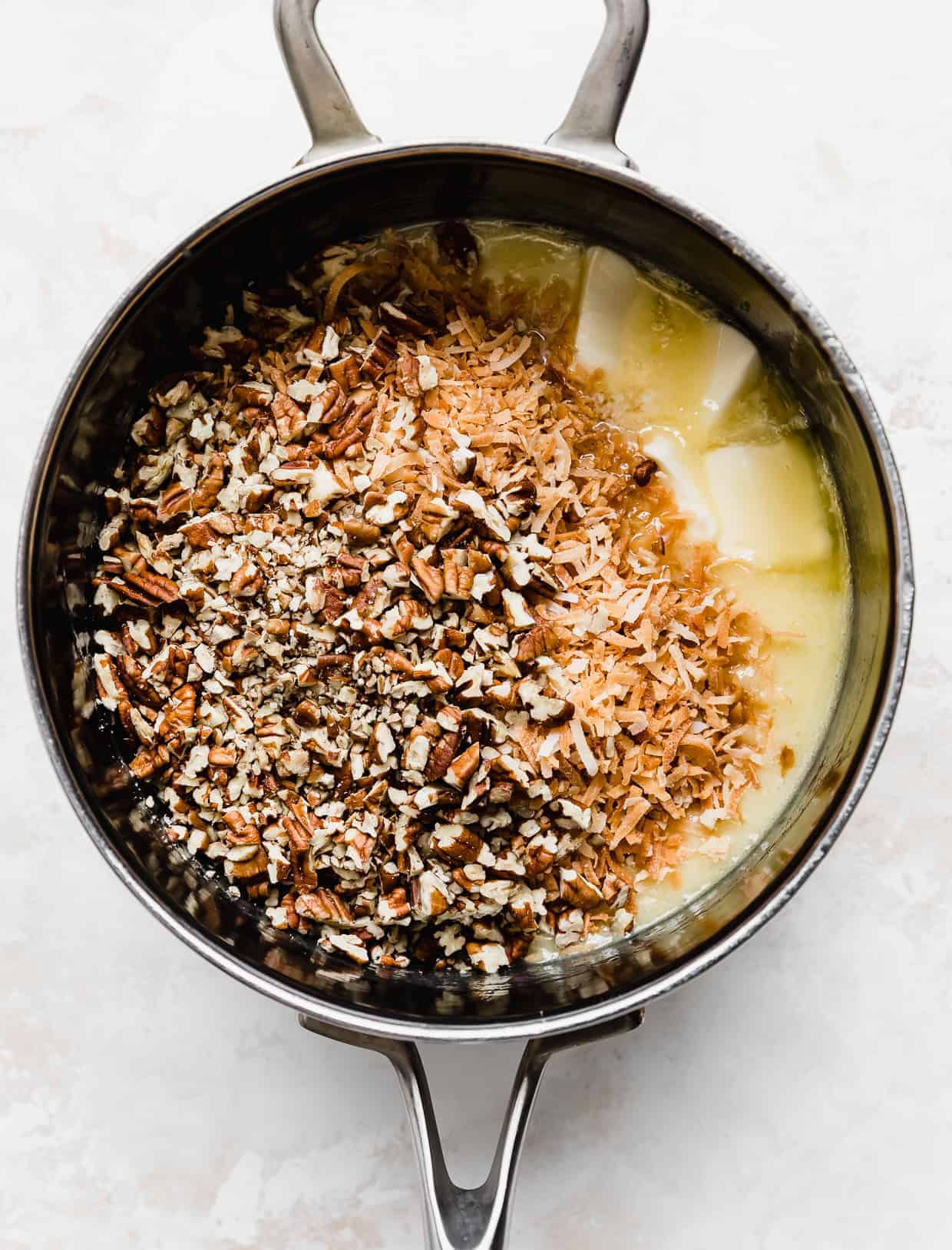 A saucepan with cubed butter, toasted coconut, and chopped pecans in it.