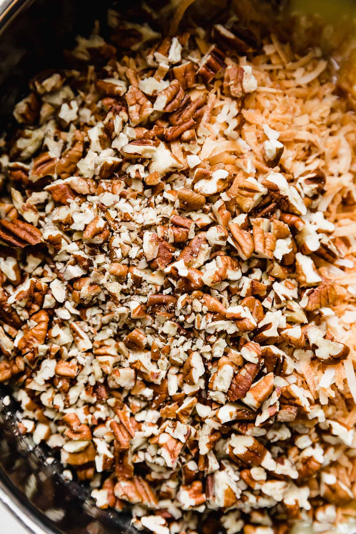A close up photo of finely chopped brown pecans.