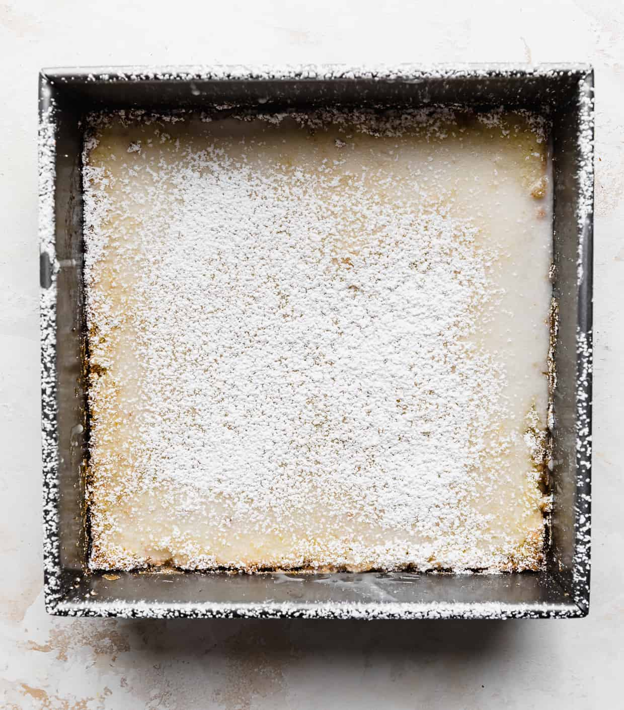 A square pan of lemon bars topped with a sprinkling of powdered sugar.