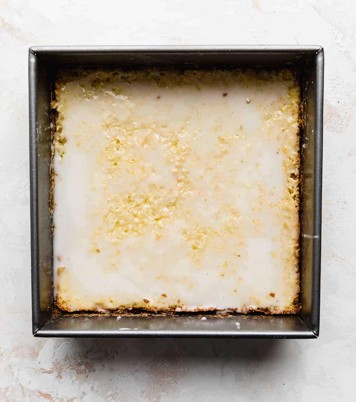 A square pan against a white background with glazed lemon bars in the pan.