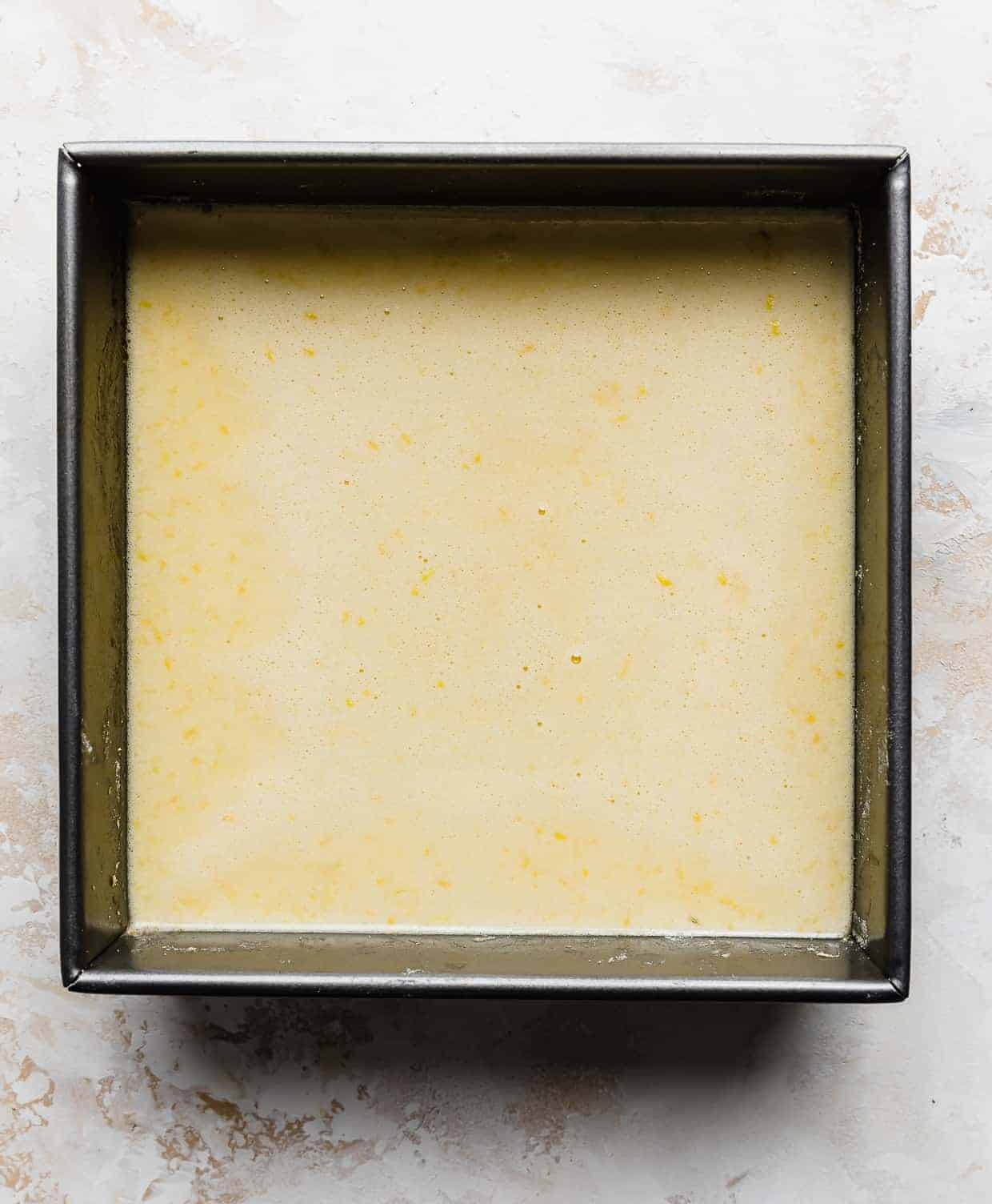 A square pan with unbaked yellow lemon bar filling in the pan.