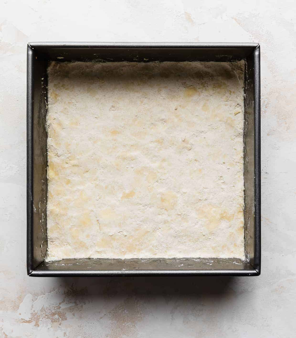 A square pan with a layer of sweetened shortbread crust lining the bottom of the pan.
