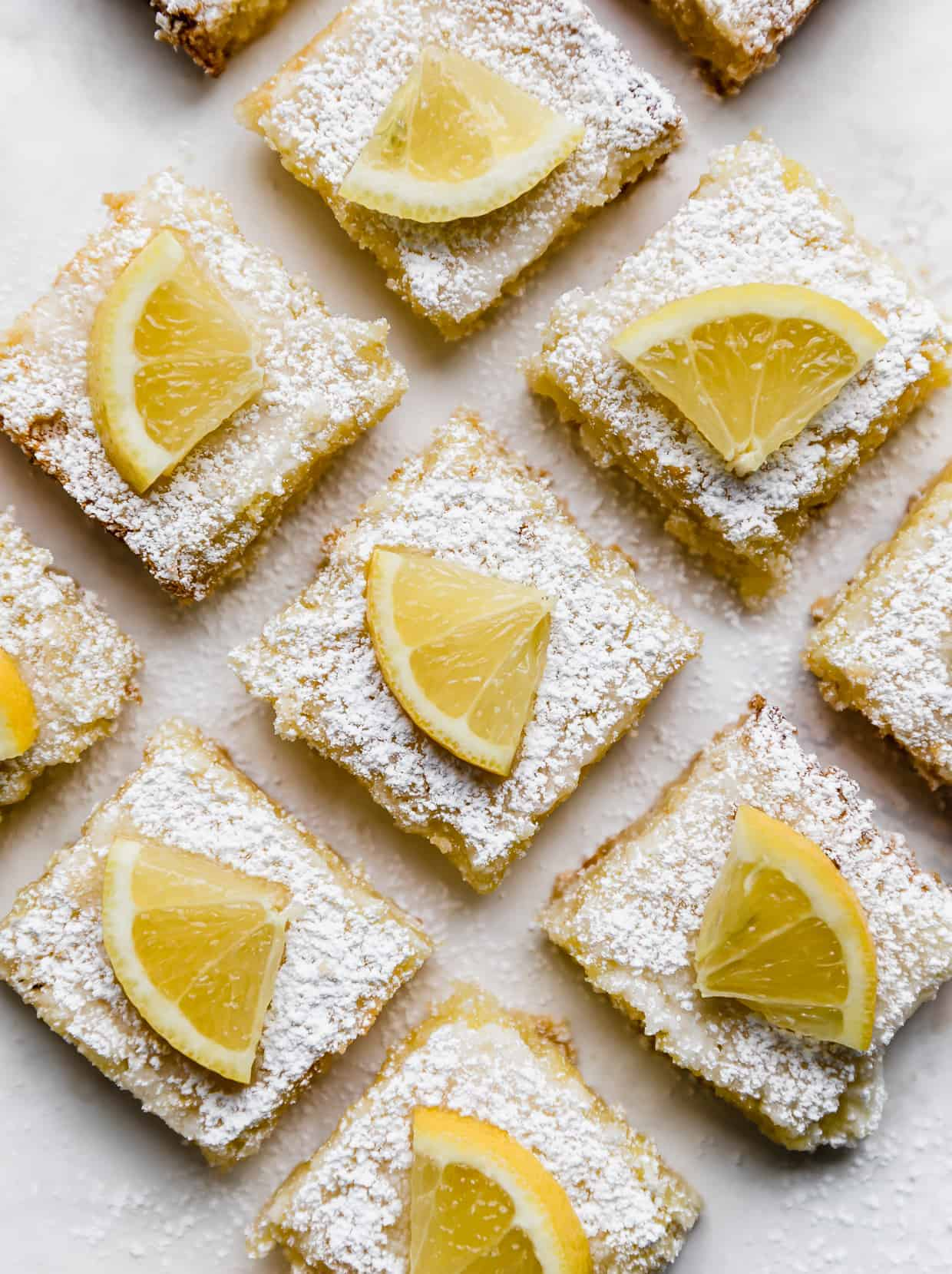 Overhead photo of lemon bars against a white background with sliced lemon wedges on top of the powdered sugar dusted lemon squares.